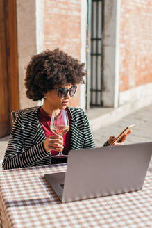 Freelancer Young Woman Using Smartphone and drinking a wine - CAVF75706