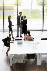 Business people shaking hands in modern office conference room - BMOF00286