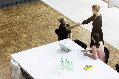 Businesswomen shaking hands in modern office conference room - BMOF00289