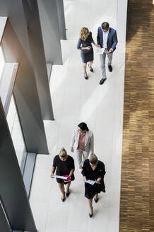 Business people walking in modern office building - BMOF00298