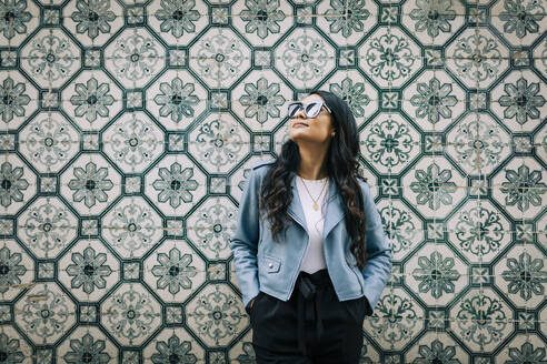 Portrait of young woman wearing light blue leather jacket and sunglasses in front of Azulejo wall, Lisbon, Portugal - DCRF00029
