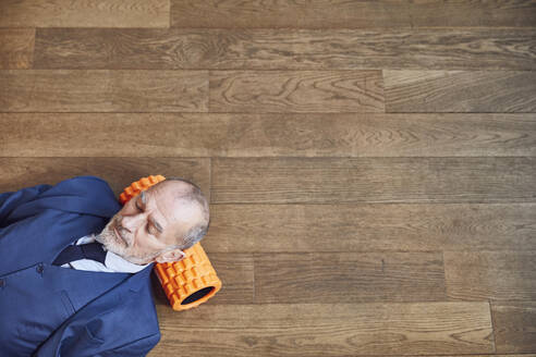 Senior businessman relaxing on wooden floor, resting on fascia roll - MCF00615