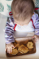 Baby girl sitting in high chair eating homemade oatmeal cookies with hands, Top view - GEMF03456