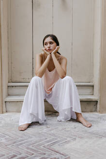 Portrait of melancholic teenage girl wearing white culottes sitting barefoot on steps outdoors - TCEF00210