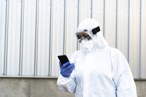 Female scientist wearing protective suit and mask and looking at smartphone - ERRF02728