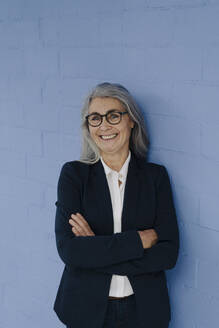 Portrait of smiling grey-haired businesswoman standing at a blue wall - GUSF03356