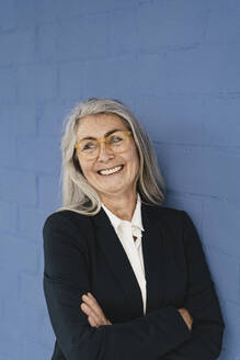 Portrait of smiling grey-haired businesswoman standing at a blue wall - GUSF03362