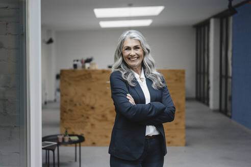 Portrait of smiling grey-haired businesswoman in a loft office - GUSF03398