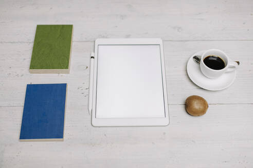 Tablet, cup of coffee, kiwi and samples on wooden surface - GUSF03425