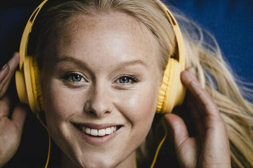 Portrait of a smiling young woman listening to music with headphones - GUSF03437
