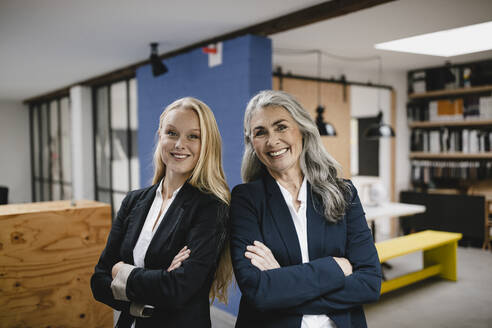 Portrait of happy mature and young businesswoman in loft office - GUSF03443
