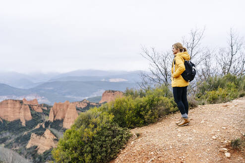 Female hiker on a viewpoint, looking to Mina de Oro Romana, former gold mine, Las Medulas, Castile and Leon, Spain - DGOF00531