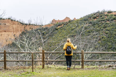 Female hiker on a viewpoint, looking to Mina de Oro Romana, former gold mine, Las Medulas, Castile and Leon, Spain - DGOF00534