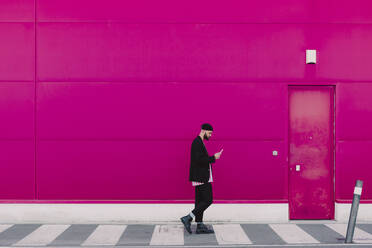 Businessman using smartphone and walking along a pink wall - ERRF02780