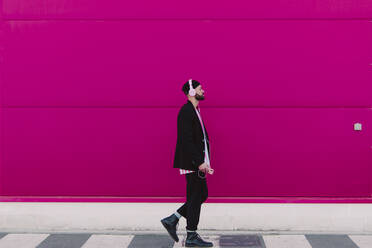 Young man with headphones and smartphone walking along a pink wall - ERRF02783