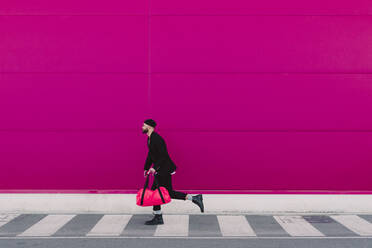 Young man with travelling bag running in front of a pink wall - ERRF02792