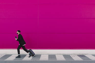 Young man with trolley walking along a pink wall, holding reusable cup - ERRF02798