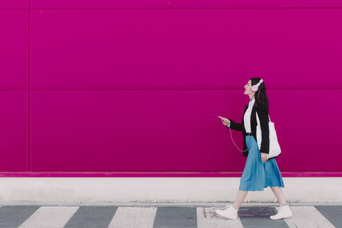 Young woman walking along pink wall, using smartphone and listening to music - ERRF02801