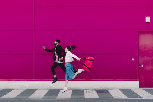 Man and woman running along a pink wall - ERRF02804