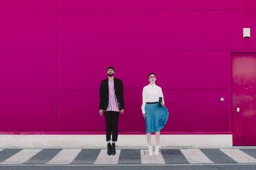 Man with smartphone and woman with coffee to go jumping in front of a pink wall - ERRF02807