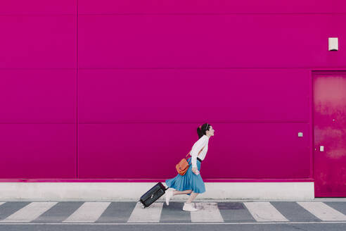 Young woman with smartphone running with trolley along a pink wall - ERRF02810
