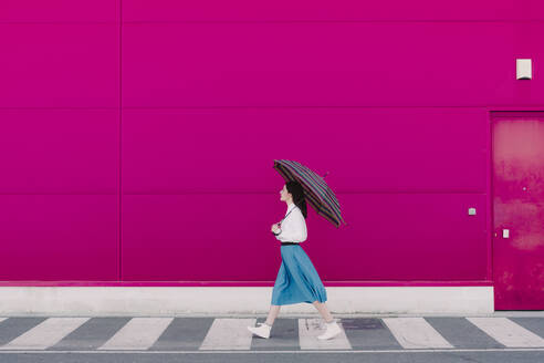Young woman with umbrella walking in front of a pink wall - ERRF02813