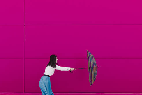 Young woman holding umbrella in front of a pink wall - ERRF02816