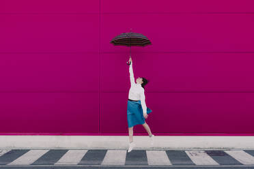 Young woman jumping with umbrella in front of a pink wall - ERRF02819