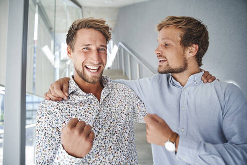 Portrait of two happy young businessmen embracing - PNEF02361