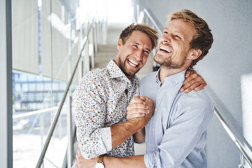 Portrait of two happy young businessmen shaking hands - PNEF02364