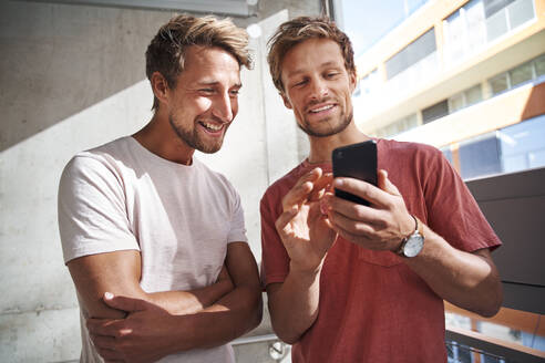 Two happy young men sharing smartphone - PNEF02385
