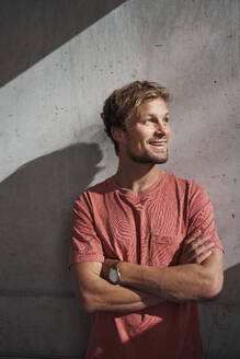 Portrait of man wearing red t-shirt at concrete wall - PNEF02391