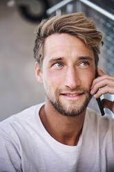 Portrait of young man wearing t-shirt talking on the phone - PNEF02400