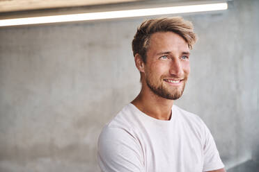 Portrait of smiling young man wearing white t-shirt - PNEF02412