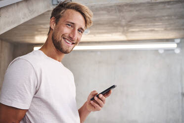 Portrait of attactive young man wearing white t-shirt holding smartphone - PNEF02415