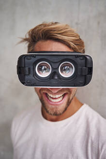 Laughing young man wearing virtual reality goggles - PNEF02418