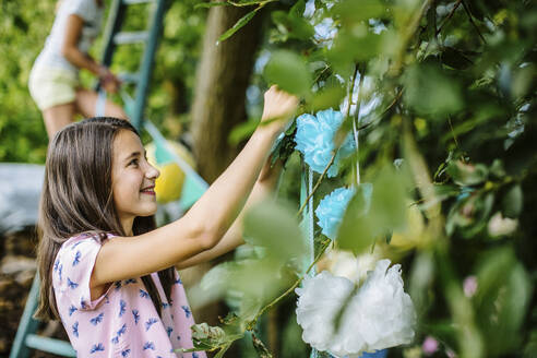 Girl decorating the garden for a birthday party - SODF00620