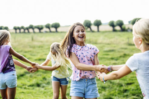 Happy girls dancing on a field together - SODF00635