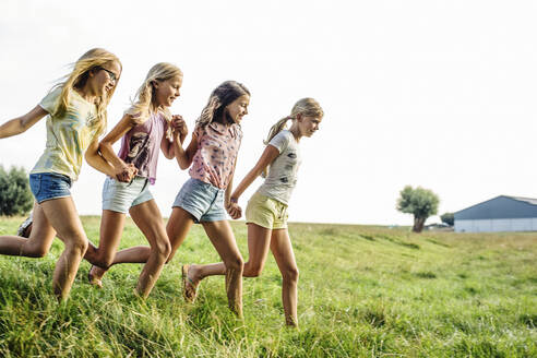 Happy girls running on a field in the countryside - SODF00641