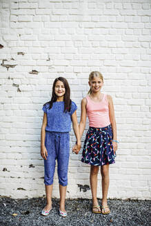 Portrait of two smiling girls standing hand in hand at a wall - SODF00683