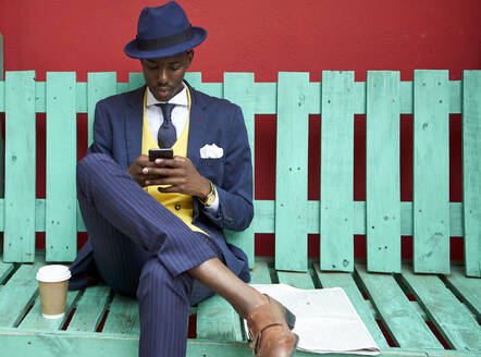 Young businessman wearing old-fashioned suit and hat sitting on a green bench checking his phone - VEGF01606