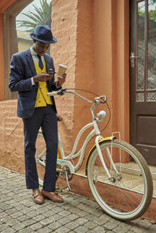 Stylish young businessman with bicycle wearing old-fashioned suit checking his phone - VEGF01615