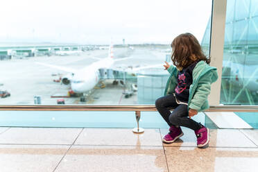 Girl sitting at the airport in front of a plane, ready to travel - GEMF03466