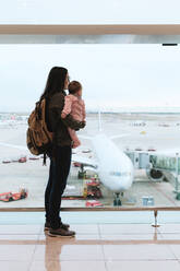 Mother with baby girl and backpack at the airport in front of a plane at airport in Barcelona, Spain - GEMF03469
