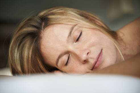 Portrait of blond young woman lying down with closed eyes - PNEF02442