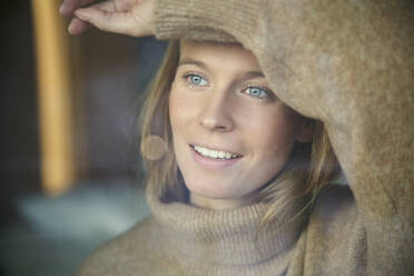Portrait of smiling blond young woman behind windowpane - PNEF02448