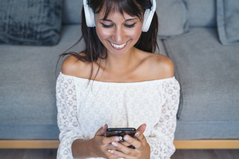Happy young woman listening to music with headphones in the living room at home - MPPF00529