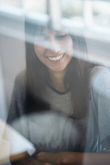Portrait of smiling young woman behind windowpane - MPPF00535