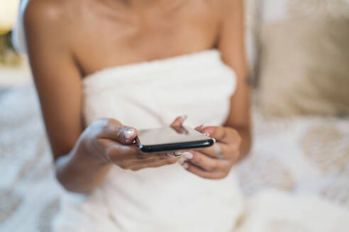 Clos-up of young woman wrapped in a towel sitting on bed holding cell phone - MPPF00538