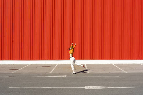 Young woman dancing in front of a red wall - ERRF02824
